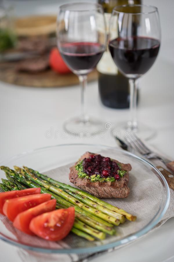 Gourmet steak with grilled asparagus and glass of red wine on white table stock photography