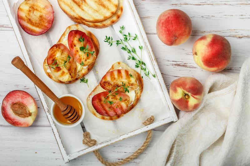 Gourmet summer Breakfast - sandwiches bread toast, bruschetta with grilled peaches royalty free stock images
