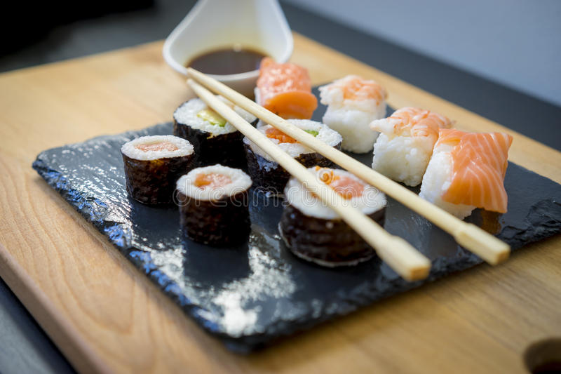 Gourmet, Sushi on a wooden table on black slate plate with soy s stock photography