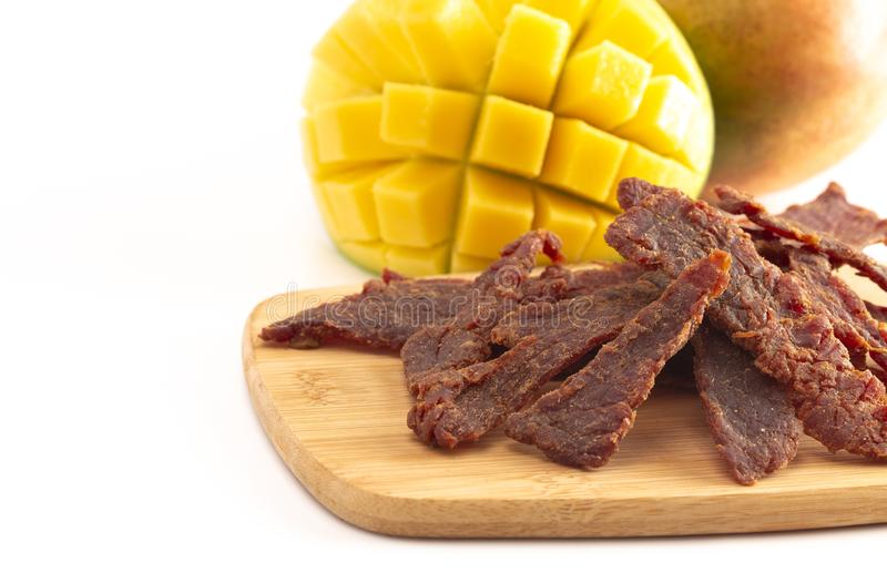 Gourmet Sweet Mango Flavored Beef Jerky on a Cutting Board royalty free stock image