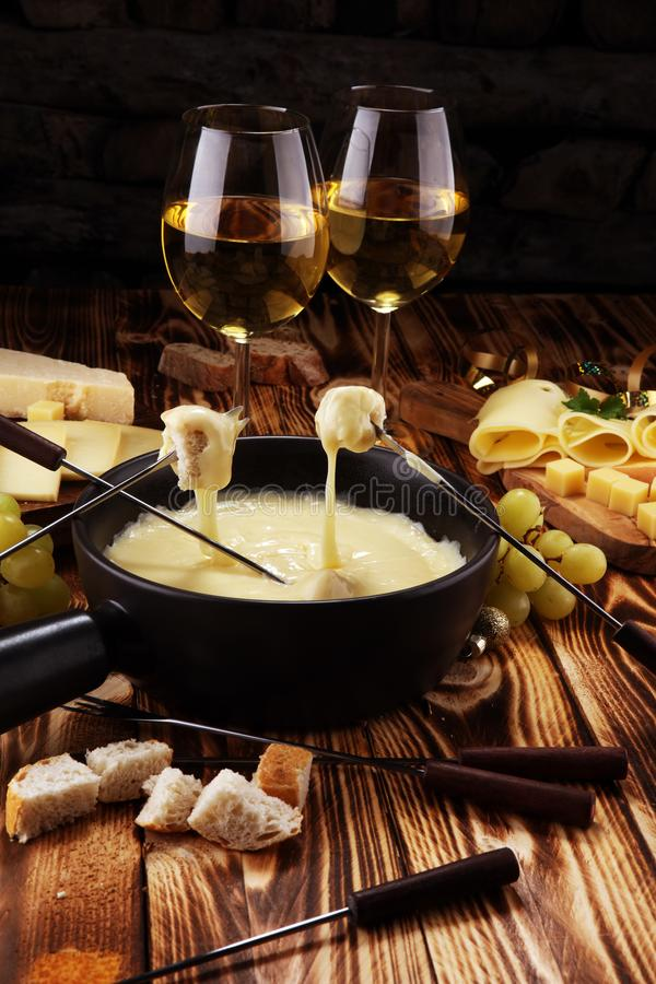 Gourmet Swiss fondue dinner on a winter evening with assorted cheeses on a board alongside a heated pot of cheese fondue with two royalty free stock images