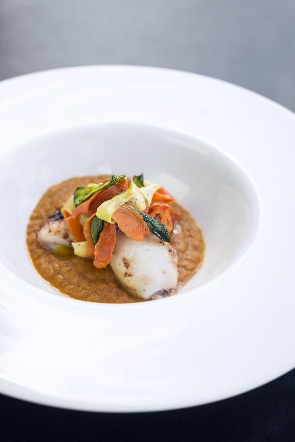 Gourmet- tioarmad bläckfisk för fusionkokkonst med inlagda grönsaker i pumpa royaltyfri foto