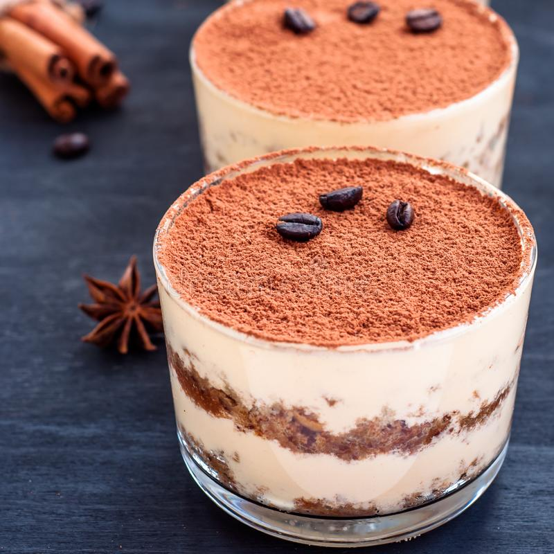 gourmet tiramisu dessert in a glass sprinkled with cocoa and decorated with coffee beans on a dark background, luxury dessert royalty free stock photography