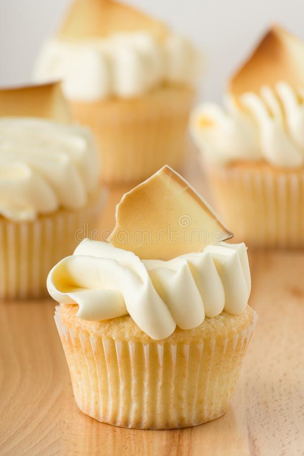 Gourmet Vanilla Cupcakes With Buttercream Frosting And White Chocolate Garnish. On Wooden Table stock images