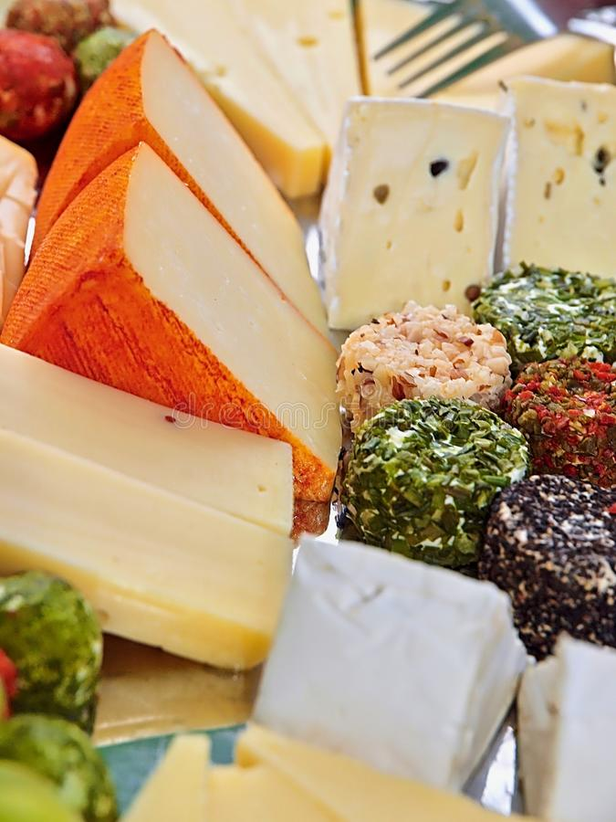 Variety of delicious cheese on a party plate. Gourmet variety of cheese, gouda, cheddar, pepper, cheese balls on a party plate royalty free stock photos
