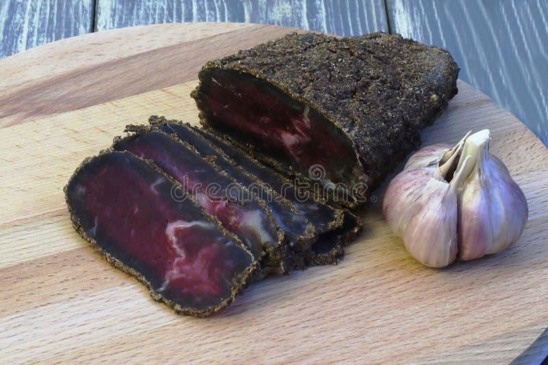 gourmet Viande sèche parfumée arrosée avec les épices et la coupe dans les tranches minces et une tête d'ail sur un conseil en bo photos stock