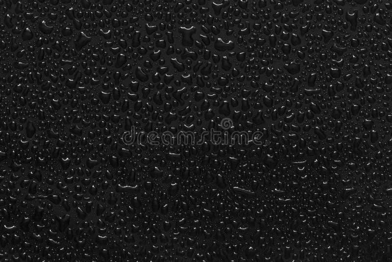 Gouttelettes d'eau sur le noir photos stock