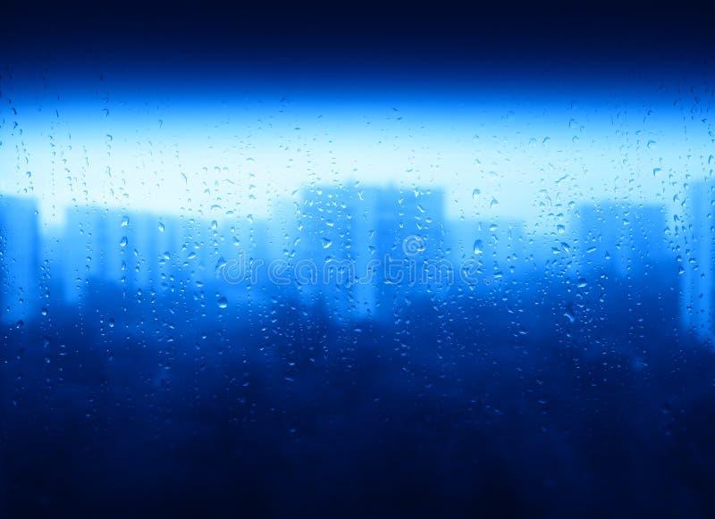 Gouttes de pluie bleues sur le fond de texture de ville de fenêtre photographie stock