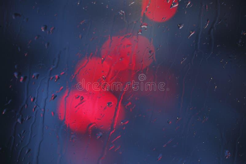 Gouttes de pluie et lumières rouges images stock