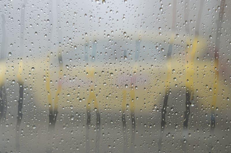 Gouttes de pluie sur le verre de fenêtre avec le contour d'un taxi photographie stock libre de droits