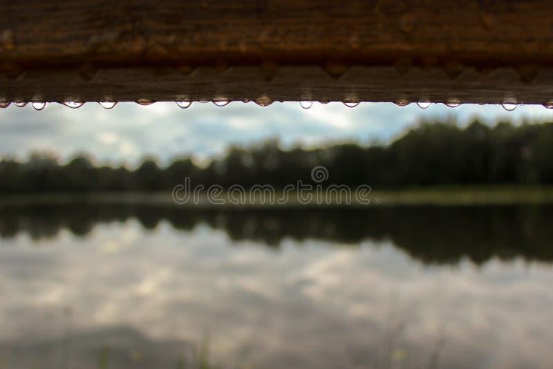 Gouttes de pluie tombant de la planche en bois image stock