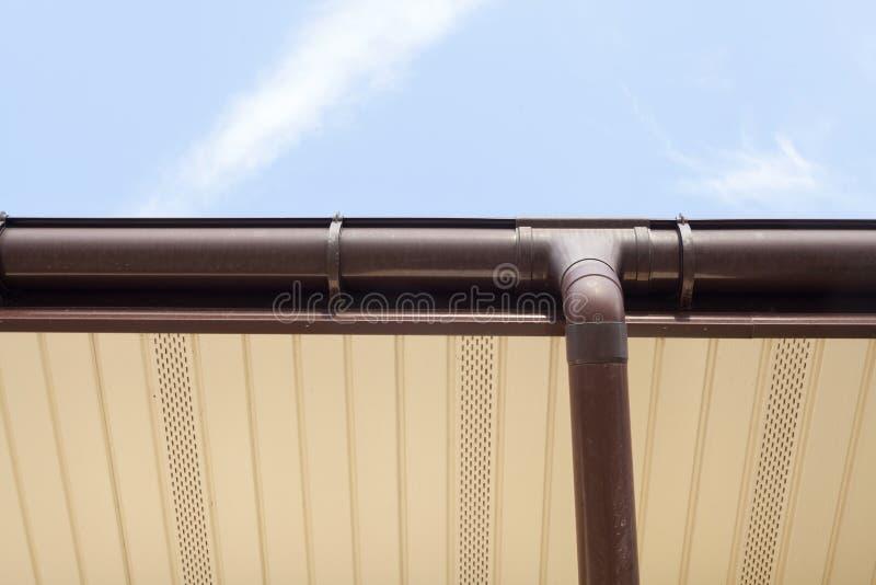 Gouttières à la maison, gouttières, système en plastique de gouttières, gouttières et tuyau de drainage extérieur contre le ciel  images libres de droits