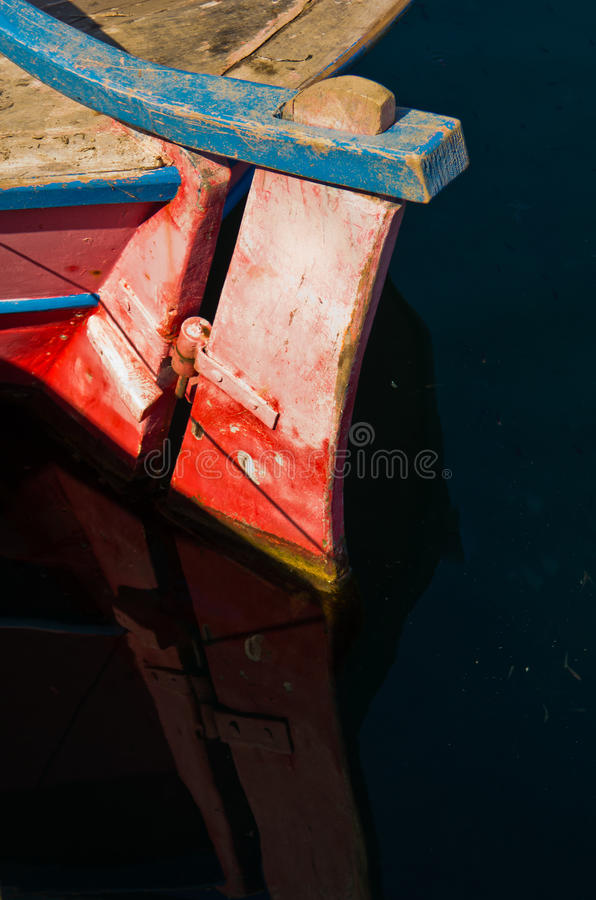 Gouvernail de direction rouge d'un vieux bateau de pêche et de sa réflexion image libre de droits