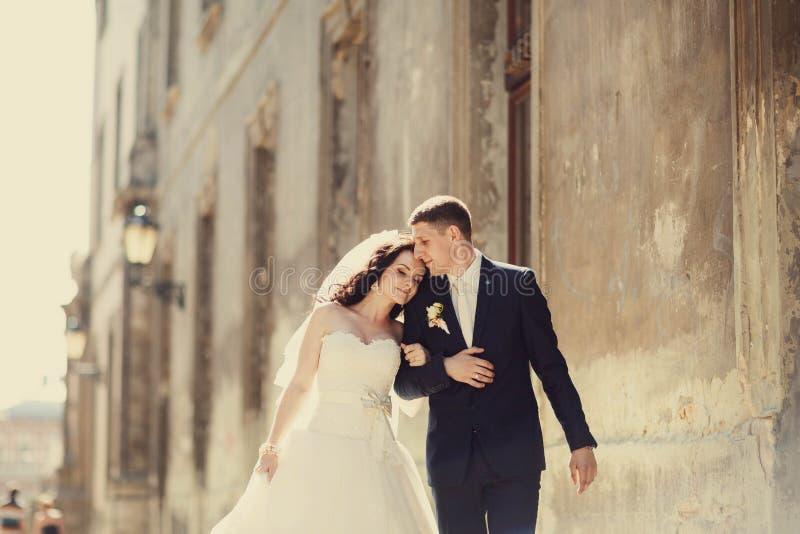 Governi huging baciando la sposa vicino alla parete all'aperto Leopoli fotografia stock libera da diritti
