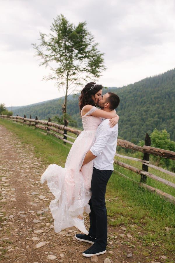Governi il bacio la sua bella sposa Coppie che camminano in montagne immagini stock libere da diritti