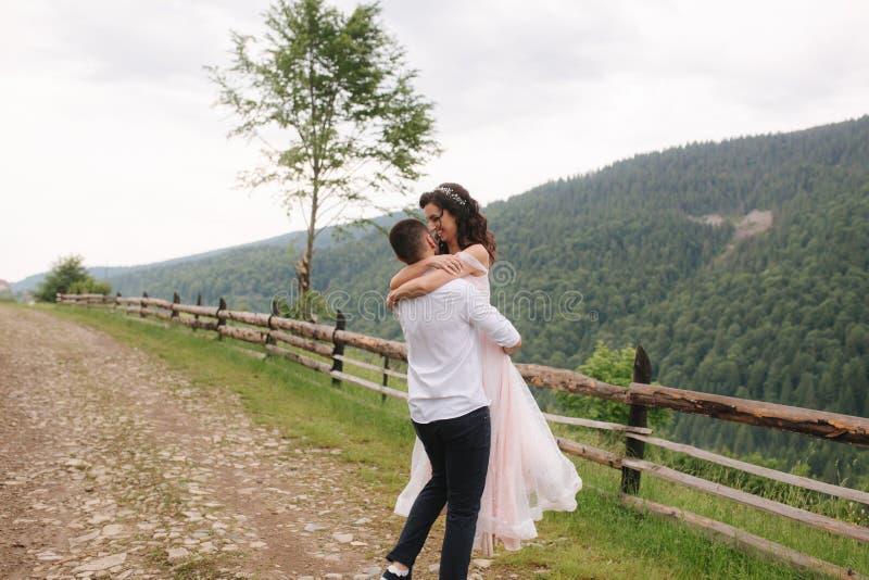 Governi il bacio la sua bella sposa Coppie che camminano in montagne fotografie stock libere da diritti