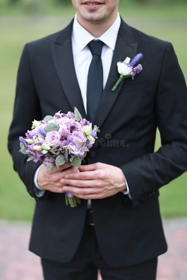 Governi il vestito nero d'uso e leghi la conservazione del mazzo dei fiori immagini stock