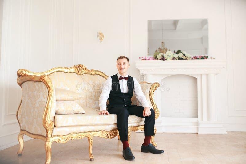 Governi la seduta sul sofà che aspetta la sposa sul suo giorno delle nozze alla sposa sorridente ed aspettante dello smoking di n immagini stock