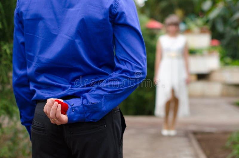 Governi nascondere la fede nuziale dietro il suo parte posteriore ed andare offrirlo ad una sposa fotografie stock libere da diritti