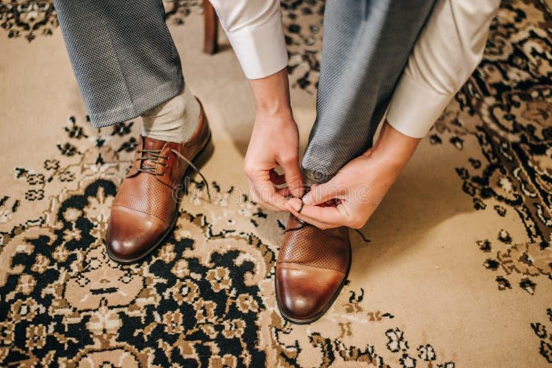 Governi tradizionalmente le scarpe marroni dei pizzi su un tappeto sul giorno delle nozze immagini stock