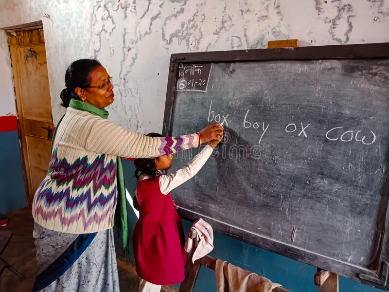Government school teacher teaching to indian girl at classroom in india January 2020 royalty free stock photography