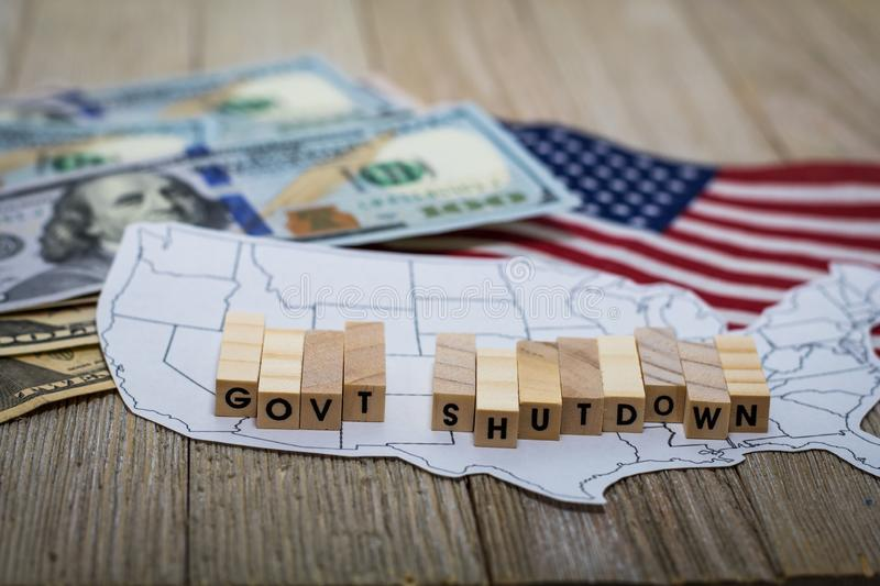 Government Shutdown USA concept with American flag and money bills on white background and wooden board stock photography