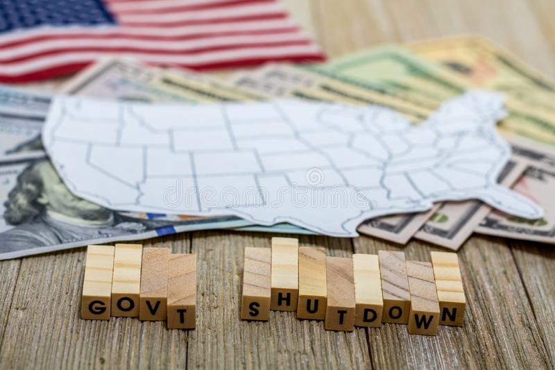 Government Shutdown USA concept with American flag and money bills on white background and wooden board stock photos