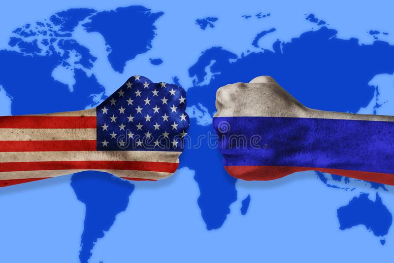Governments conflict concept. Male fists colored in USA and Russian flags on world map background. Conflict between USA and Russia stock photography