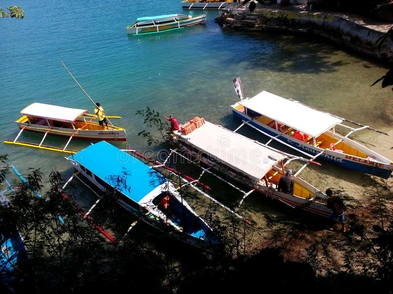 Outrigger boats beached for sightseeing stop on Governor`s Island, Hundreed Islands National Park, Alaminos, Philippinnes royalty free stock photo