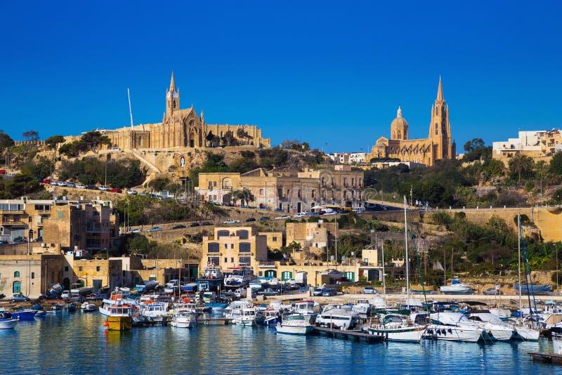 Gozo, Μάλτα - το λιμάνι Mgarr με την άποψη της εκκλησίας η κυρία Lourdes μας στην κορυφή στοκ εικόνα