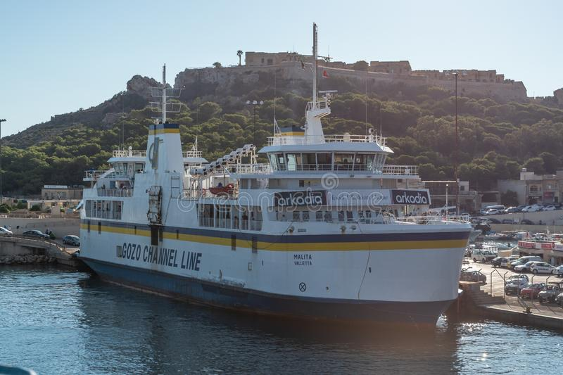 Gozo Channel Line Moored in Mgarr. 30th SEP 2018 Mgarr Gozo. Gozo Mgarr Harbour breakwater and another ship moored with chambre fort in view. on a sunny summer royalty free stock photos