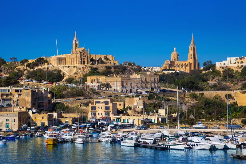 Gozo, Malta - el puerto de Mgarr con la vista de la iglesia nuestra señora de Lourdes en el top imagen de archivo