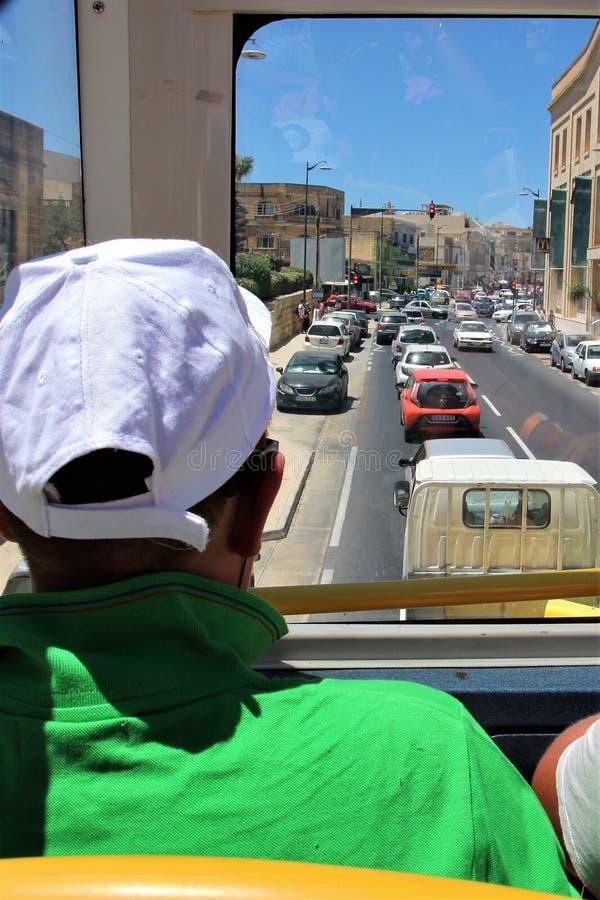 Gozo, Malte, juillet 2016 Le garçon regarde la ville de la fenêtre d'un autobus de touristes photos libres de droits