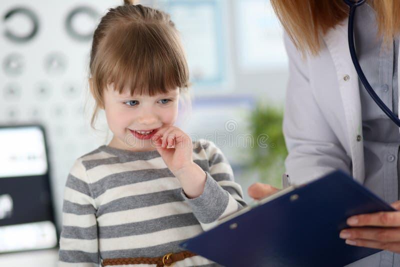 Gp bonito da ajuda da menina para completar o formul?rio de inscri??o paciente fotos de stock