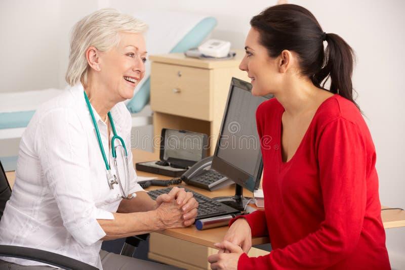 GP británico que habla con el paciente de la mujer imágenes de archivo libres de regalías