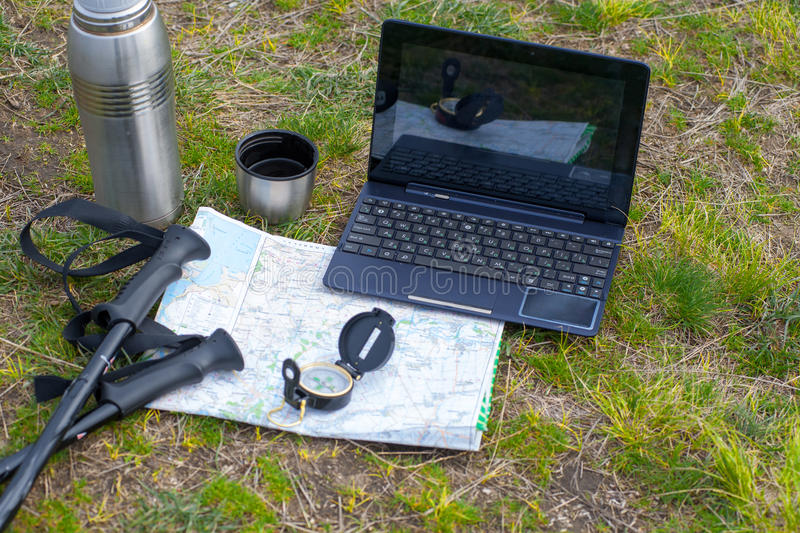 GPS navigation, travel and tourism concept02. Phone, laptop, map, compass and a tent on the grass in the camping stock image