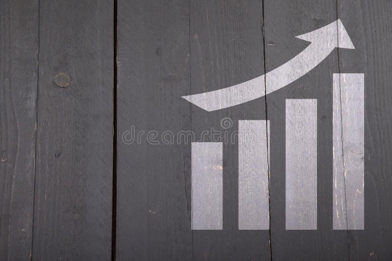 Gráfico branco com crescimento no fundo de madeira imagem de stock royalty free
