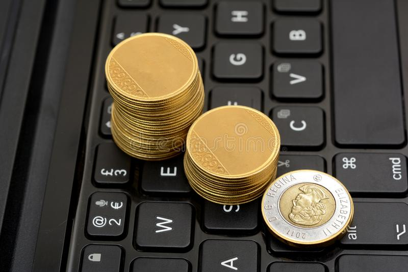 Gráfico de levantamiento de la moneda canadiense de las monedas de oro en el teclado imagenes de archivo