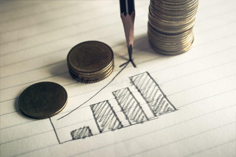 gráfico de negocio del dibujo de lápiz en el papel del cuaderno con busin de las monedas imagen de archivo libre de regalías