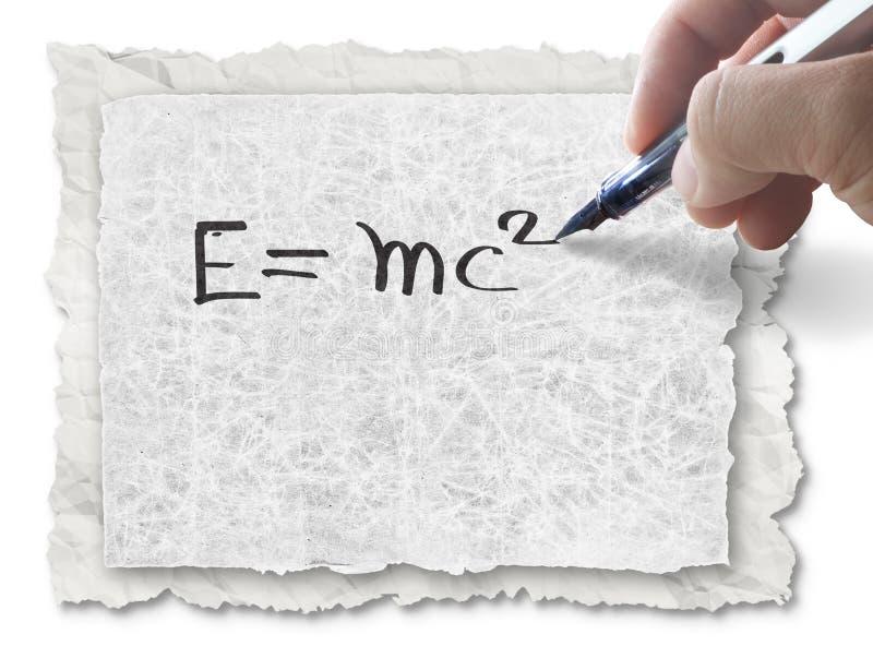 Gráfico E=mc2 de la mano en el papel fotos de archivo