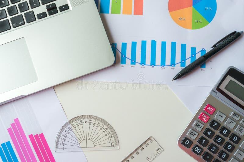 Gráfico financeiro e de negócio com portátil, calculadora, régua e prolongador fotografia de stock