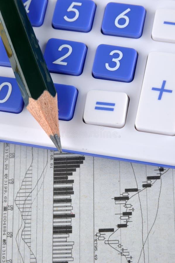Gráfico, lápiz y calculadora comunes foto de archivo