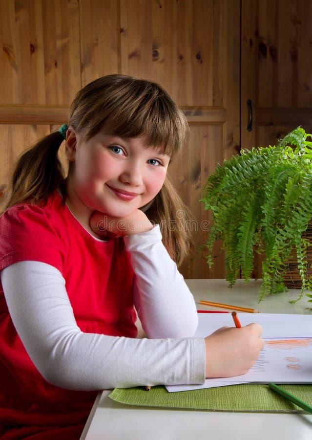 Gráfico lindo de la niña en su escritorio fotos de archivo