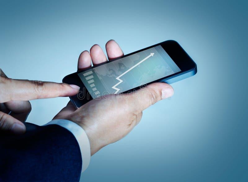 Gráfico y estadísticas del teléfono móvil del tacto del hombre de negocios que suben en el sc fotos de archivo libres de regalías