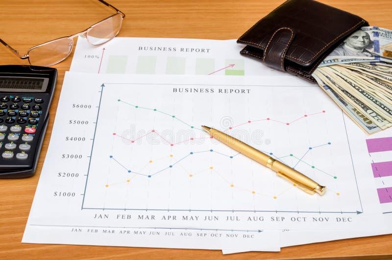 Gráficos, cartas, tabla del negocio con el dinero, calculadora y pluma imágenes de archivo libres de regalías