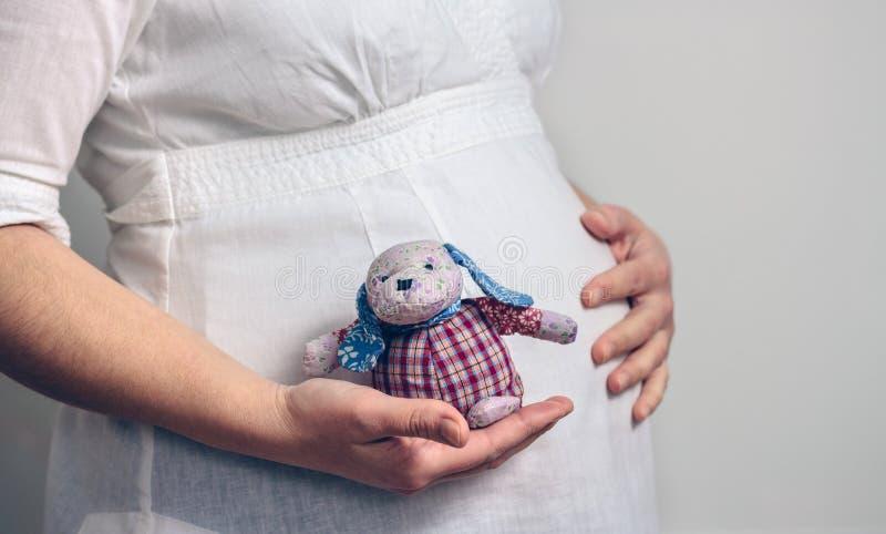 Grávido guardando uma boneca de pano do bebê fotografia de stock