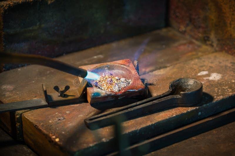 Grânulo de derretimento do ouro e da prata dos ourives em um cadinho com a foto de stock royalty free