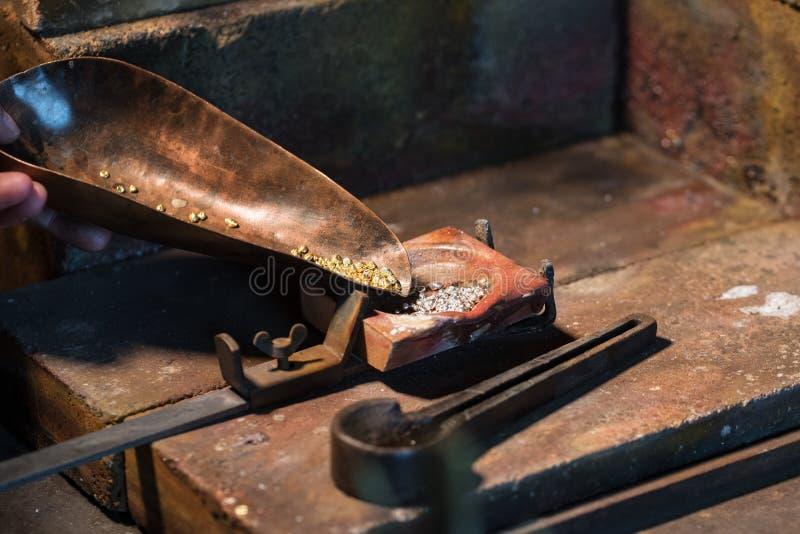 Grânulo do ouro e da prata em um cadinho para derreter uma liga, ferramentas da joia em um local de trabalho dos ourives, espaço  foto de stock royalty free