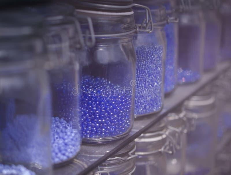 Grânulos azuis nas fileiras em prateleiras fotos de stock