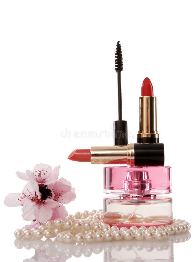 Grânulos das pérolas, cosméticos e flor da cereja foto de stock
